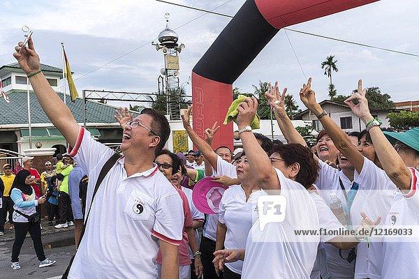 Taichi participants standing outdoors taking selfie with smartphone at Kampung Satok  Kuching  Sarawak  Malaysia..