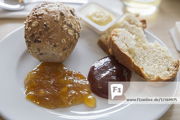 Breakfast with coffee bread butter and jam.