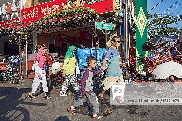 Asian family walking together along Malioboro Street. Yogyakarta  Java  Indonesia.