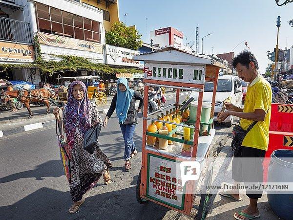 Muslim women walk by street vendor selling fresh fruit juices on Malioboro Street. Yogyakarta  Java  Indonesia.