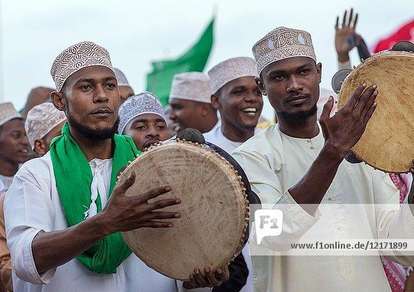 Sunni muslim men playing tambourines during the Maulidi festivities in the street  Lamu County  Lamu Town  Kenya.