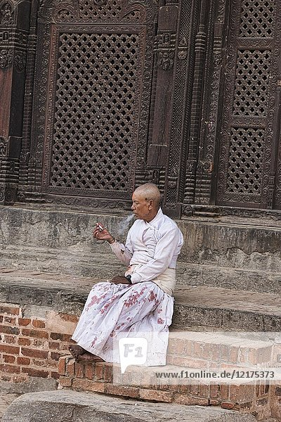 Goat butcher taking a cigarette break during Dasain Festival  Bhaktapur  Nepal.