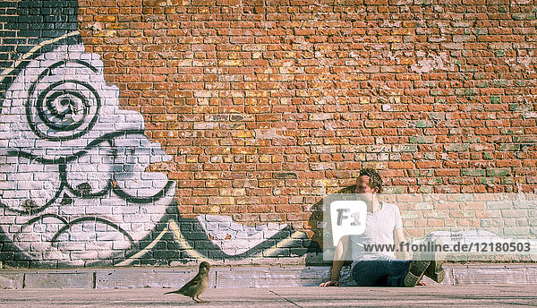 USA  New York City  man sitting at brick wall with graffiti and sparrow in foreground