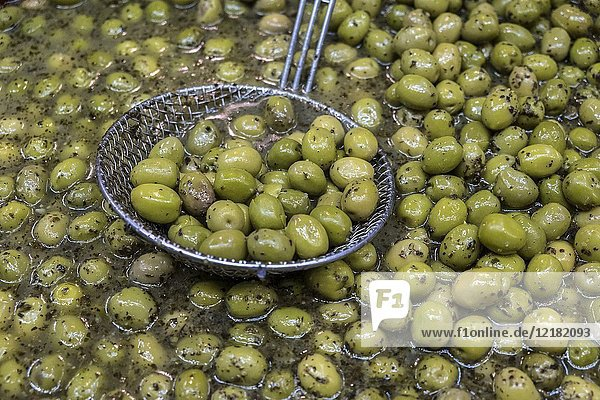 Sale of olives in the iron and glass roof of the'Les Halles' market in Narbonne France built in 1907.