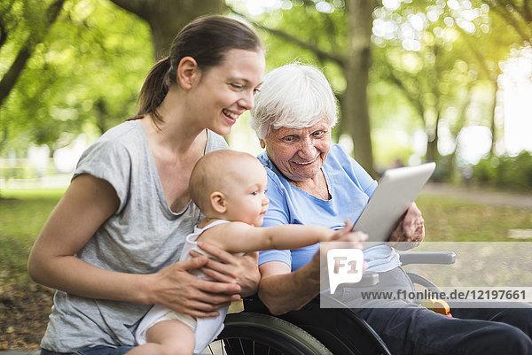 Großmutter  Tochter und Enkelin haben Spaß mit Tablette im Park