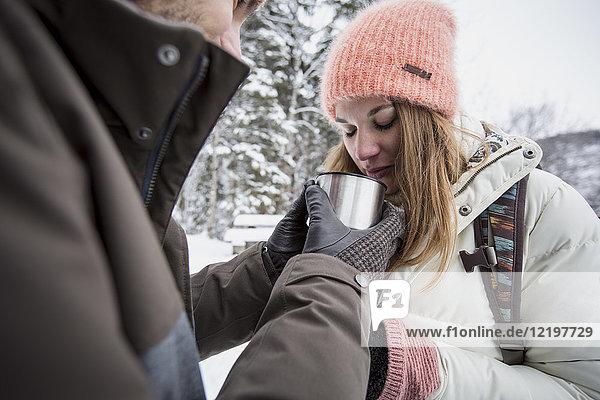 Paare teilen sich im Winter ein heißes Getränk im Freien.