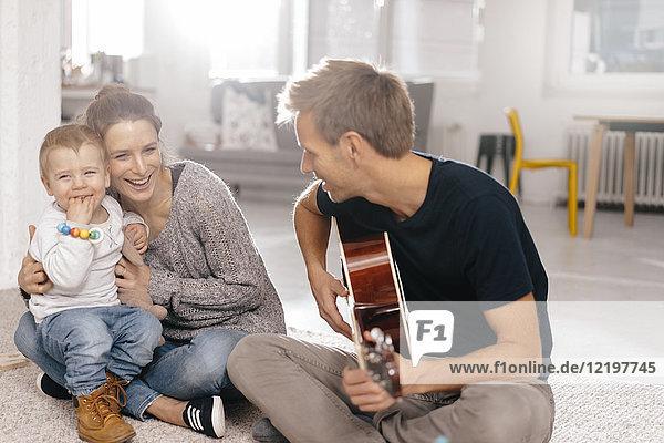Glückliche Familie sitzt auf dem Boden und Vater spielt Gitarre.