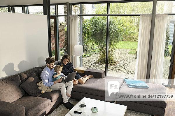 Eltern und Sohn sitzen auf dem Sofa im modernen Wohnzimmer mit Laptop zu Hause