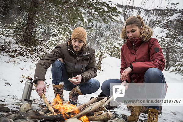 Pärchen auf einer Reise im Winter bei einer Pause am Lagerfeuer