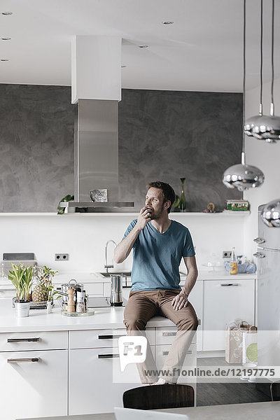 Man sitting on kitchen counter eating an apple