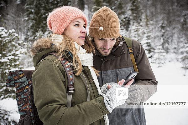 Paar auf Winterreise mit dem Handy