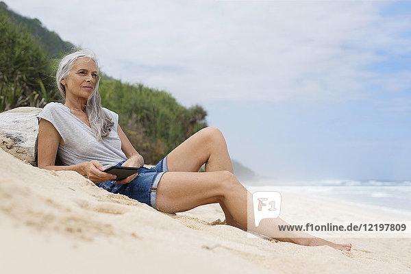 Schöne lächelnde Seniorin am Strand liegend  mit E-Book