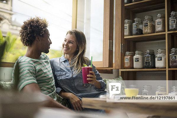 Lächelndes Paar im gemütlichen Café vor dem Fenster sitzend