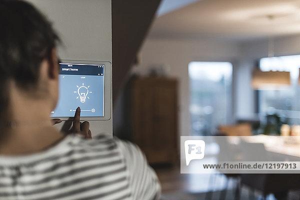 Frau mit Bildschirm und Smart Home Control Funktionen zu Hause