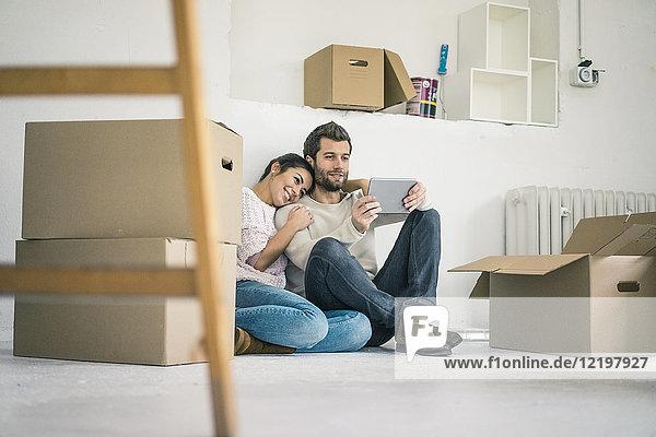 Ein Paar sitzt in einem neuen Zuhause  umgeben von Pappkartons und schaut auf das Tablett.