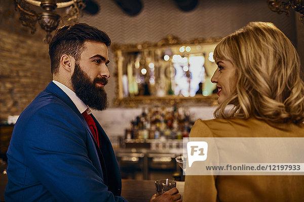 Elegantes Paar  das sich in einer Bar anlächelt.