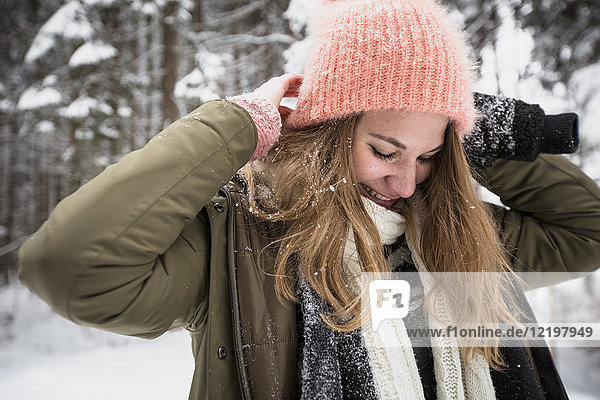 Lächelnde junge Frau im Winter im Freien