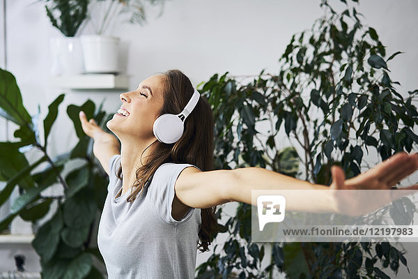 Happy young woman with oustretched arms listening to music at indoor plant