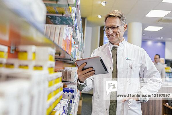 Lächelnder Apotheker im Regal mit Medikamenten in der Apotheke hält Tablette