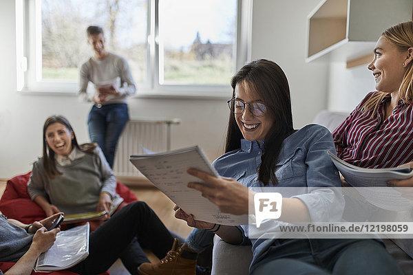 Gruppe von glücklichen Schülern im Wohnheim lernen zusammen