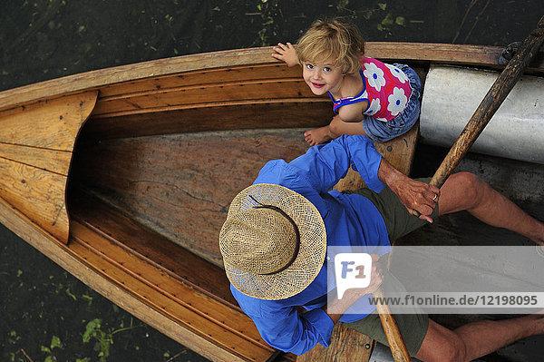 Glückliches kleines Mädchen mit ihrem Großvater im Ruderboot  Draufsicht Glückliches kleines Mädchen mit ihrem Großvater im Ruderboot, Draufsicht