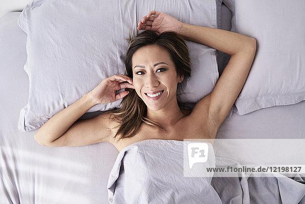 Porträt einer lächelnden Frau im Bett liegend ohne Pyjama