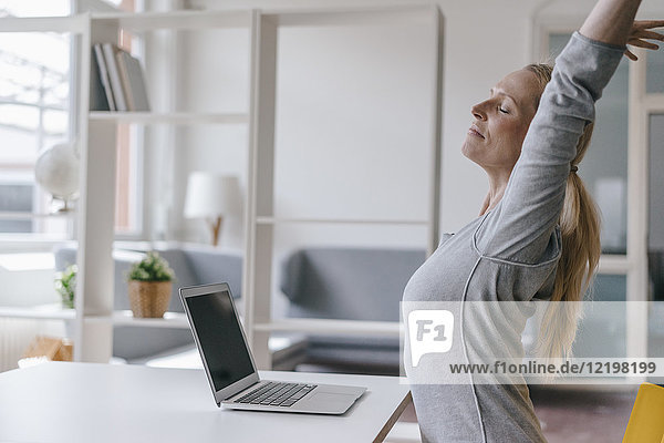 Woman with laptop at desk in office stretching