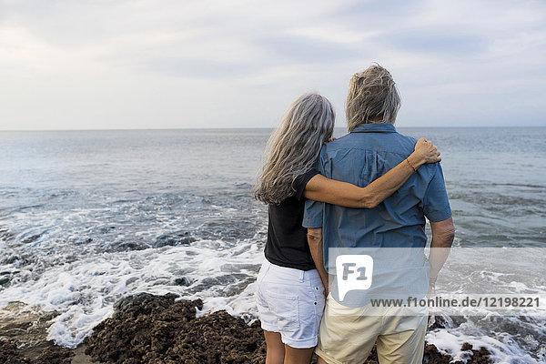 Seniorenpaar mit Blick auf den Ozean  Rückansicht