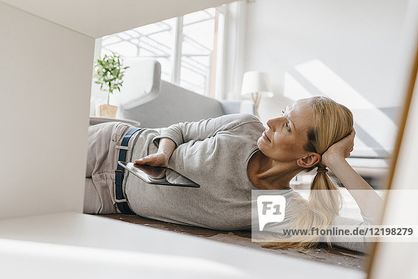 Woman lying on the floor holding tablet