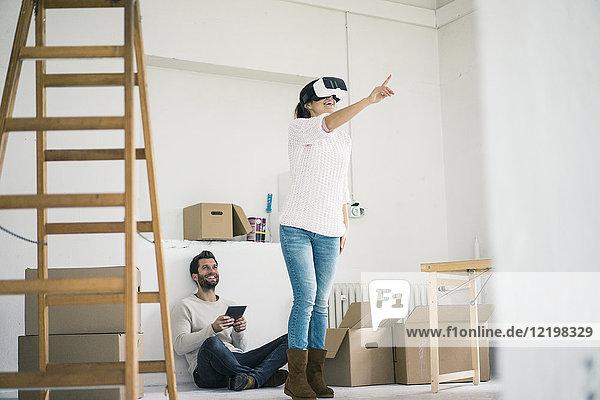 Paar in neuem Zuhause mit Frau mit VR-Brille
