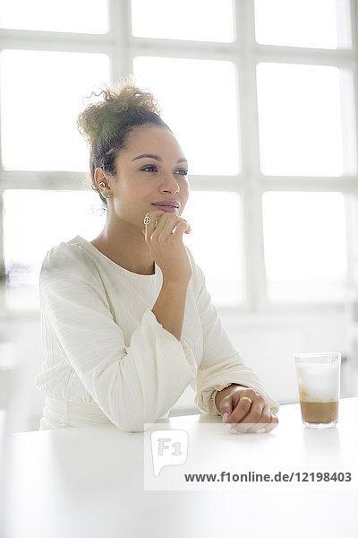 Porträt einer lächelnden jungen Frau  die mit einem Glas Kaffee am Tisch sitzt.