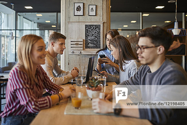 Gruppe von Freunden sitzen zusammen in einem Cafe mit Laptop  Smartphones und Getränken