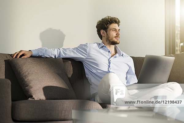 Man sitting on couch at home with laptop