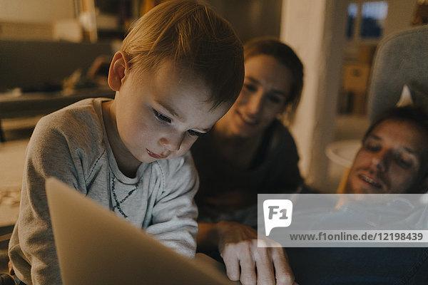 Familie mit Laptop auf der Couch im Dunkeln
