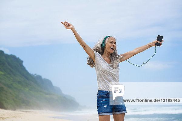 Seniorin mit Kopfhörer tanzt am Strand