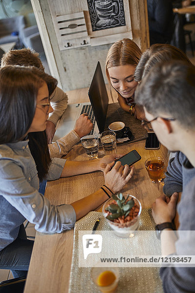 Group of friends sitting together in a cafe with laptop  smartphone and drinks