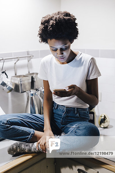 Young woman sitting on kitchen worktop  checking messages on smartphone