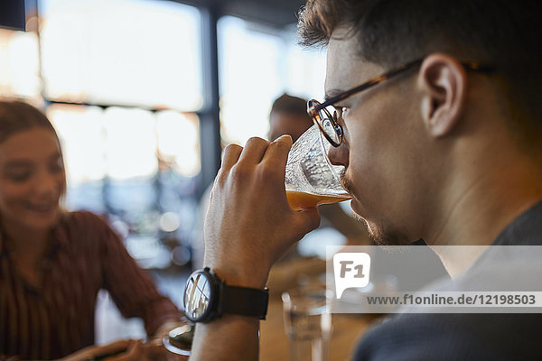 Young man drinking glass of juice in a cafe with friends in background