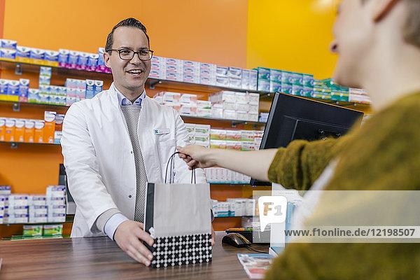 Apotheker geben Beutel mit Medikamenten an Kunden in der Apotheke