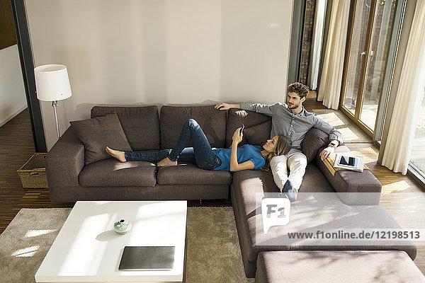 Paar mit Tablett und Smartphone zum Entspannen auf dem Sofa im modernen Wohnzimmer zu Hause