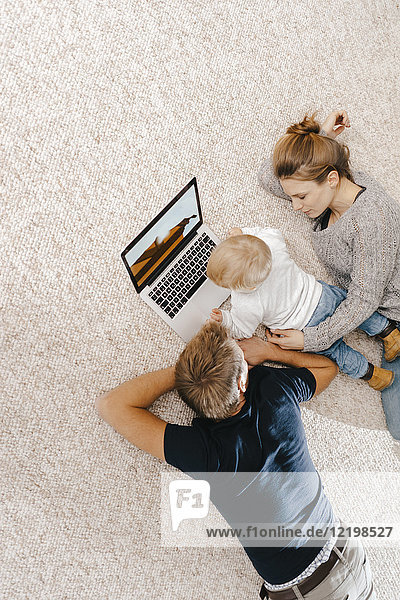 Familie mit Laptop auf dem Teppich