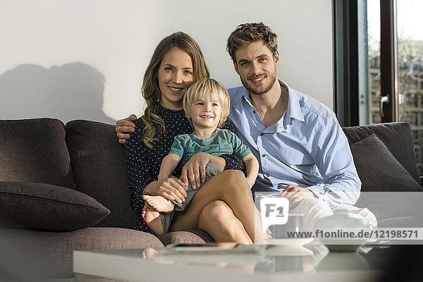 Porträt der lächelnden Eltern und des Sohnes  der zu Hause auf dem Sofa sitzt