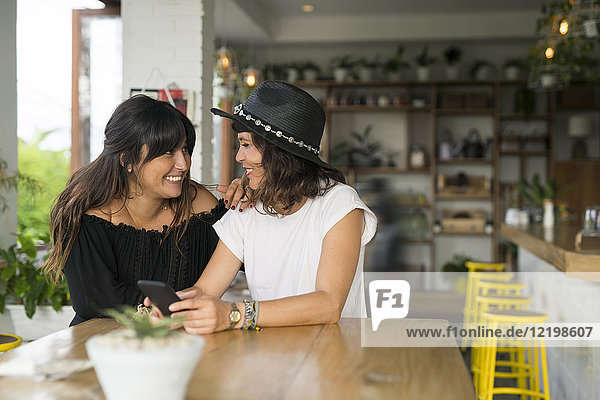 Two female friends smiling at each other in cafe with smartphone