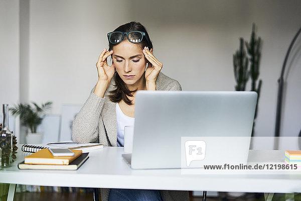 Junge Frau zu Hause mit Laptop auf dem Schreibtisch  der ihre Schläfen berührt.