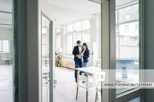 Geschäftsmann und Geschäftsfrau teilen sich Handy im Büro