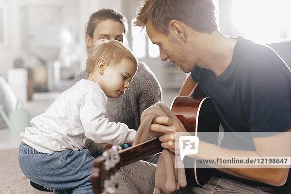 Kleines Mädchen untersucht Vaters Gitarre zu Hause