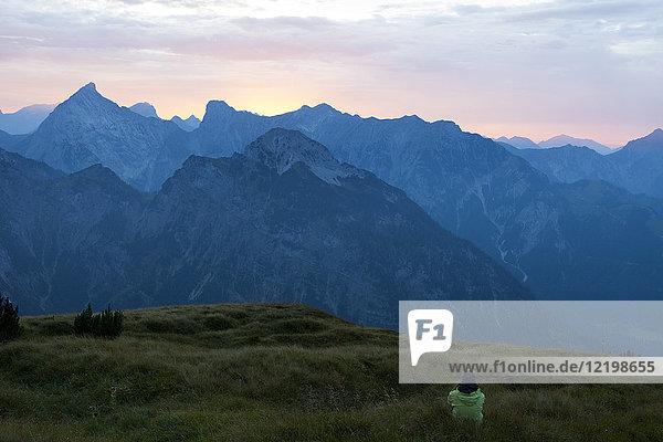 Österreich  Tirol  Wanderer in der Abenddämmerung auf der Alm