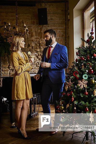 Elegantes Paar mit Getränken am Weihnachtsbaum stehend