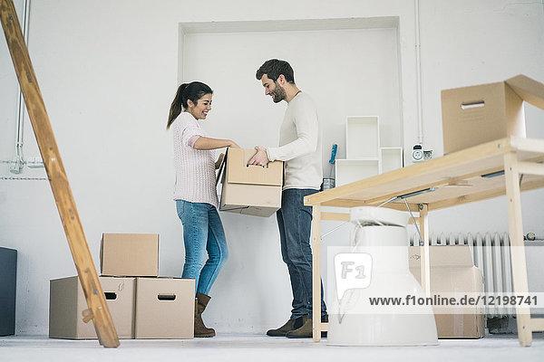 Paar zieht in ein neues Zuhause ein und packt Kartons aus.