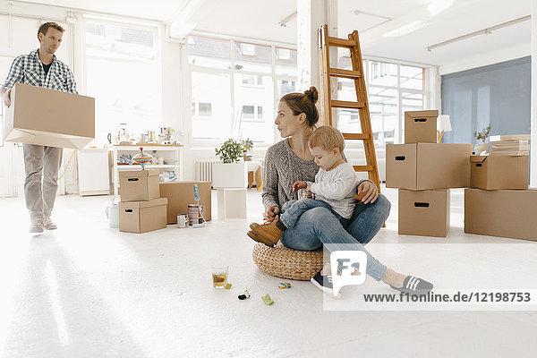 Umzug der Familie in ein neues Zuhause mit Vater mit Kartonschachtel